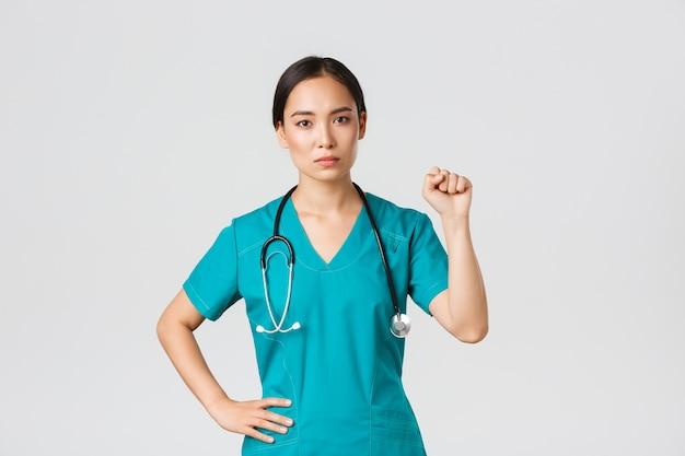 , pracownicy służby zdrowia, koncepcja pandemii. poważnie wyglądająca pewna siebie, poważna azjatycka lekarka okazuje wsparcie kolegom podczas koronawirusa, podnosząc pięść w geście jedności