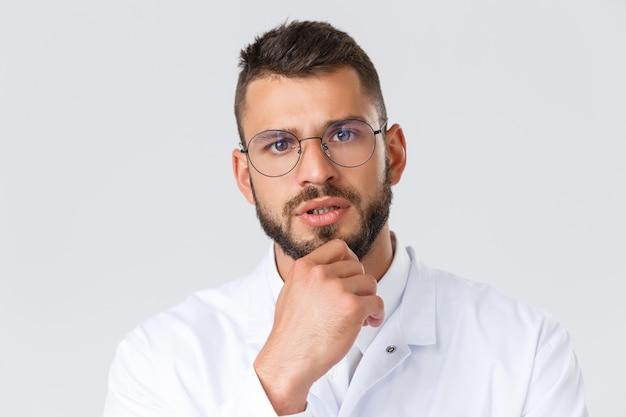 Pracownicy służby zdrowia, koronawirus, koncepcja pandemii covid-19. zbliżenie poważnie wyglądającego profesjonalnego lekarza w okularach i białym fartuchu, dotknięcie podbródka w zamyśleniu, myślenie, podejmowanie decyzji w sprawie pacjenta