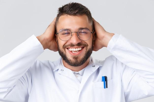 Pracownicy służby zdrowia, koronawirus, koncepcja pandemii covid-19. zbliżenie: wesoły latynoski lekarz mężczyzna w okularach i białym płaszczu, beztroski uśmiechający się z zamkniętymi oczami i rękami na głowie, radujący się.