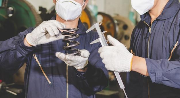 Pracownicy sprawdzają jakość, rozmiar i konstrukcję części metalowych za pomocą suwmiarki z noniuszem z metaloplastyki w fabryce. produkcja części metalowych i kontrola jakości.