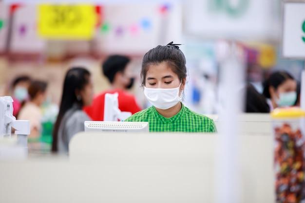 Pracownicy supermarketów i klienci w medycznych maskach ochronnych