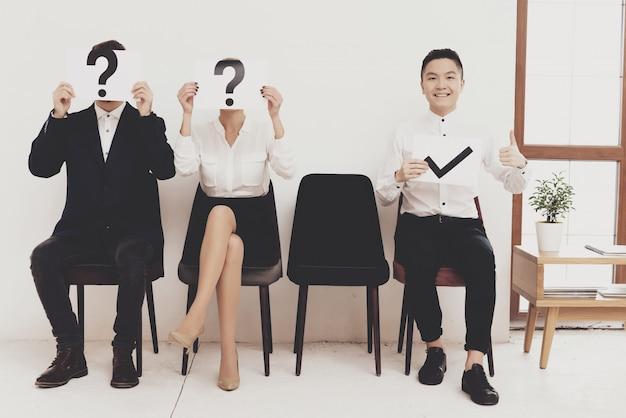 Pracownicy trzymają znaki różnych pytań