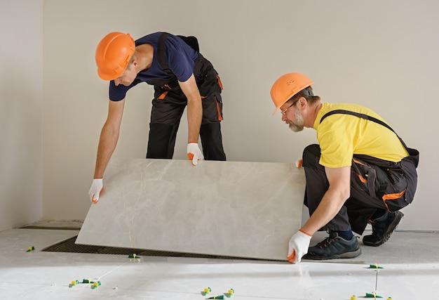 Pracownicy układają na podłodze dużą płytkę ceramiczną