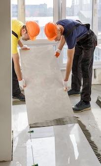 Pracownicy układają na podłodze dużą płytkę ceramiczną.