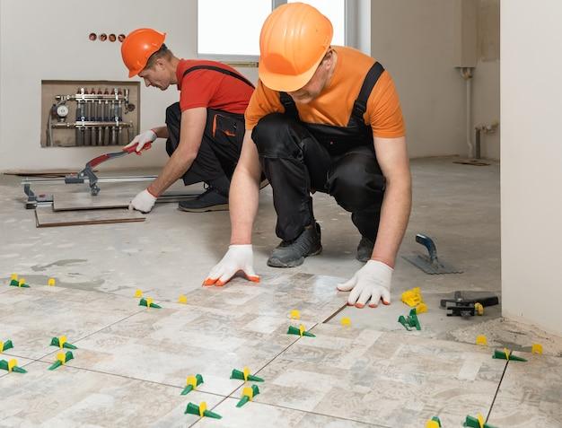 Pracownicy układają na podłodze płytki ceramiczne