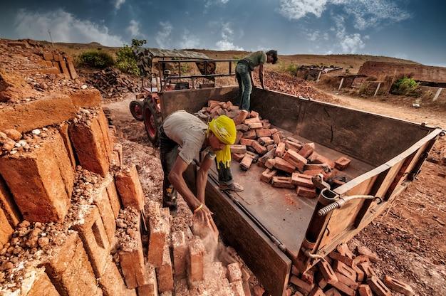Pracownicy układający gotowe cegły w pojazdach transportowych.