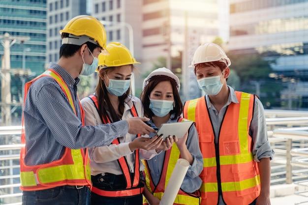 Pracownicy uzbrojeni w maskę chirurgiczną i bezpieczną białą głowę w celu ochrony przed zanieczyszczeniami i wirusami w miejscu pracy podczas obaw o pandemię kowboju