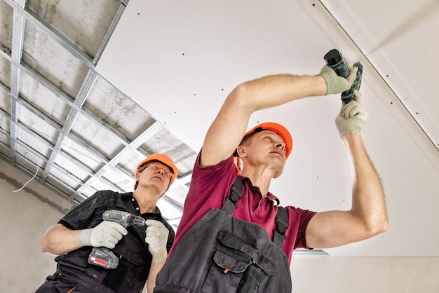 Pracownicy używają śrubokręta do mocowania płyt gipsowo-kartonowych do sufitu