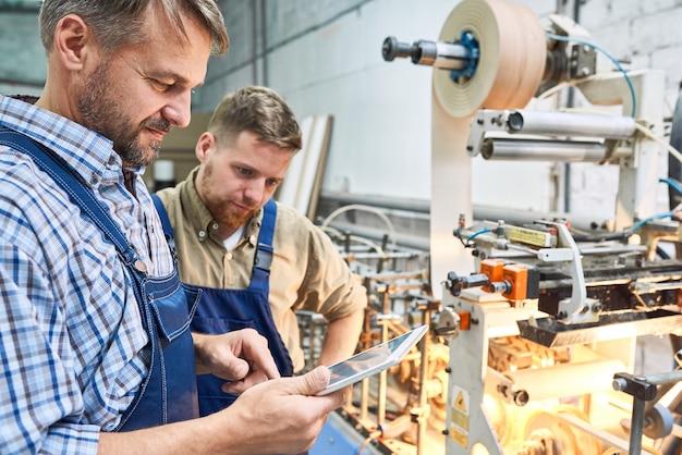 Pracownicy używający nowoczesnej maszyny w fabryce