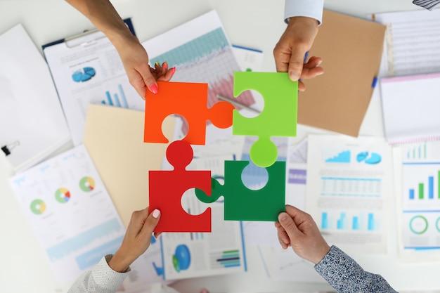 Pracownicy w biurze trzymają kolorowe puzzle i układają je w całość