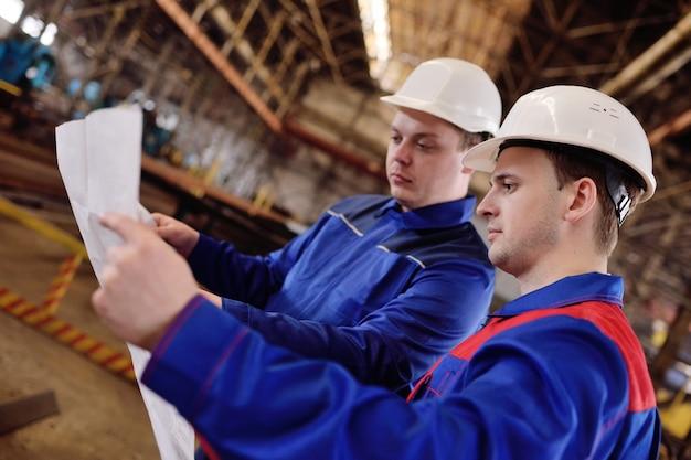Pracownicy w hełmach budowlanych z rysunkiem
