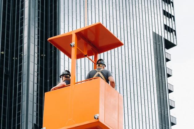 Pracownicy w kołysce konstrukcyjnej wspinają się na dźwig do dużego przeszklonego budynku. dźwig podnosi pracowników w fotelu samochodowym.
