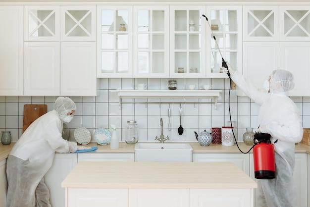 Pracownicy w kombinezonach ochronnych dezynfekują mieszkanie środkami chemicznymi