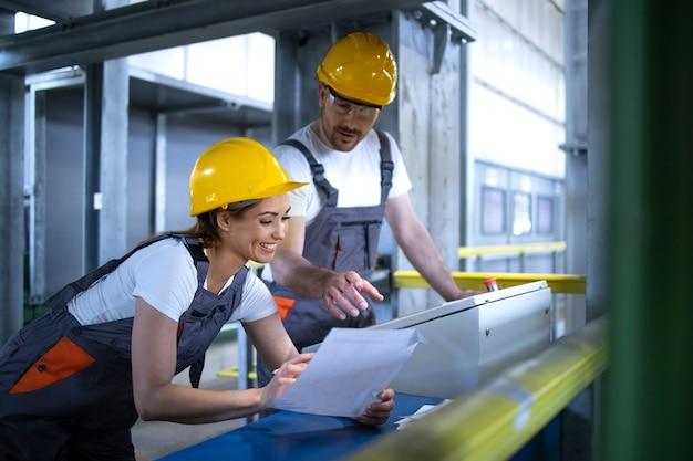 Pracownicy w mundurach i kaskach obsługujący maszyny na centralnym komputerze fabrycznym