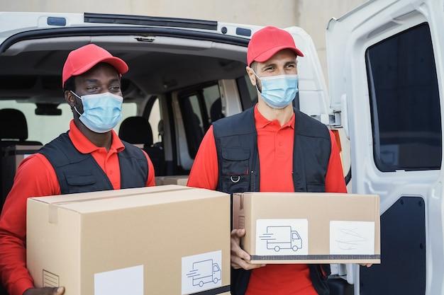 Pracownicy wielorasowi dostarczający pudła w maskach ochronnych podczas epidemii koronawirusa — skoncentruj się na prawej twarzy mężczyzny