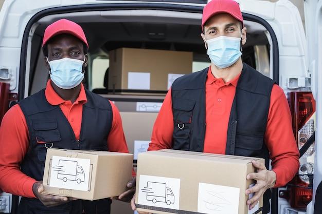 Pracownicy wielorasowi dostarczający pudła w maskach ochronnych podczas epidemii koronawirusa — skoncentruj się na twarzach
