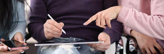 Pracownicy wskazują na ekran tabletu podczas omawiania gorących tematów