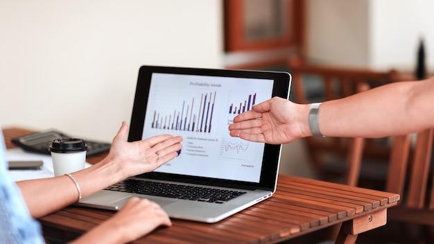 Pracownicy wskazujący na ekran laptopa z danymi finansowymi