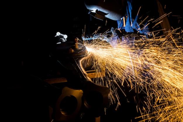 Pracownicy wykonują rowki drutami spawalniczymi z węglem iskrowym