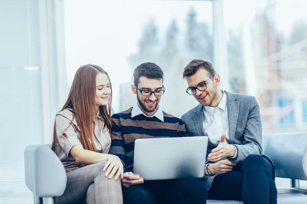 Pracownicy z laptopem siedzący w holu biura