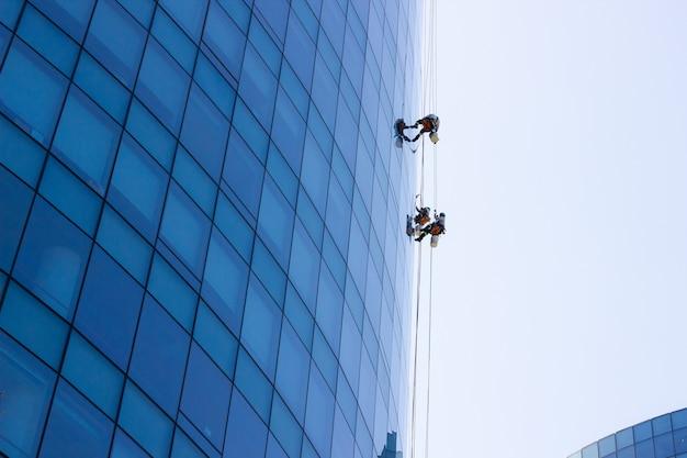 Pracownicy zajmujący się myciem okien wiszący na zewnątrz budynku biurowego z niebieskim szkłem ryzykowne, niebezpieczne koncepcje pracy