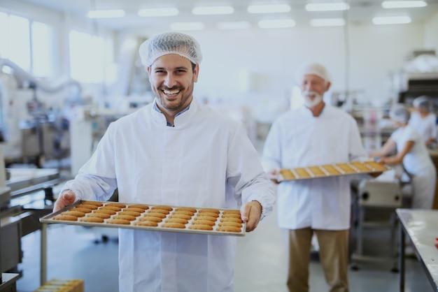 Pracownicy zakładu spożywczego w sterylnych mundurach niosący tace z ciasteczkami. selektywne skupienie się na młodszym pracowniku.