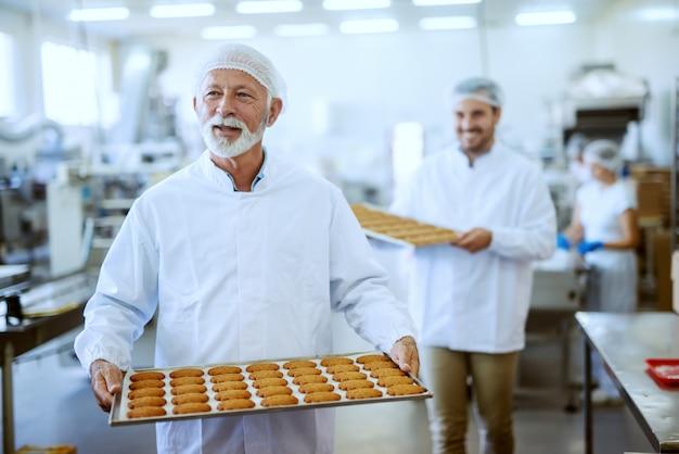 Pracownicy zakładu spożywczego w sterylnych mundurach niosący tace z ciasteczkami. selektywne skupienie się na starszym dorosłym pracowniku.