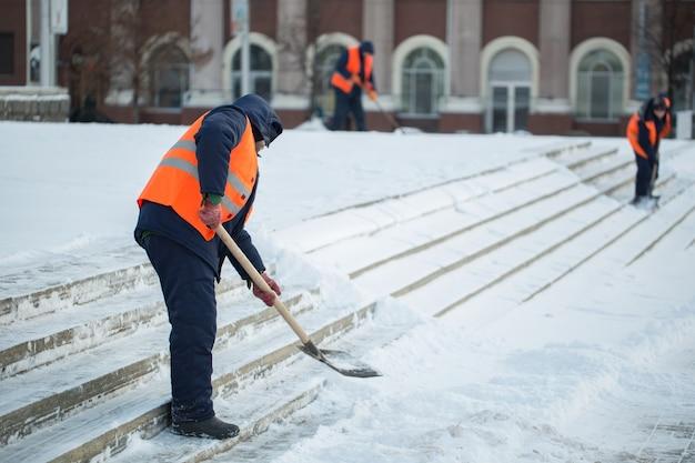 Pracownicy zamiatają śnieg z drogi w zimie, czyszczenie drogi przed burzą śnieżną.