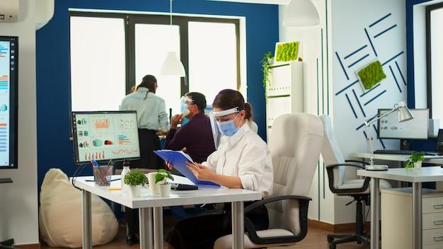 Pracownicy zespołu w nowym normalnym biurze, tworzący strategię finansową, noszący maskę ochronną. pracownicy z wizjerami pracujący w korporacyjnej przestrzeni roboczej z poszanowaniem dystansu społecznego, analizujący dane i wykresy.