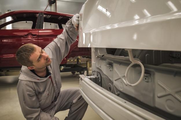 Pracownicza lakiernia karoserii sprawdza jakość malowanej powierzchni