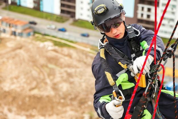 Pracownik alpinizmu przemysłowego w mundurze na elewacji budynku mieszkalnego podczas pracy w wieżowcu. robotnik dostępu linowego na ścianie domu. koncepcja przemysłowych prac urbanistycznych. skopiuj miejsce na stronę