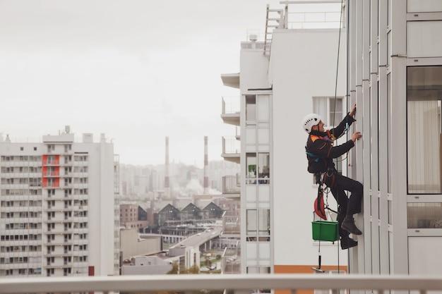 Pracownik alpinizmu przemysłowego wisi nad budynkiem elewacji mieszkalnej podczas mycia przeszklenia elewacji zewnętrznej. robotnik dostępu linowego wisi na ścianie domu. koncepcja prac urbanistycznych. skopiuj miejsce na stronę