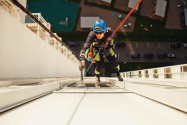 Pracownik alpinizmu przemysłowego wisi nad budynkiem mieszkalnym podczas mycia przeszklenia elewacji zewnętrznej. robotnik dostęp linowy wisi na ścianie domu. koncepcja prac urbanistycznych. skopiuj miejsce