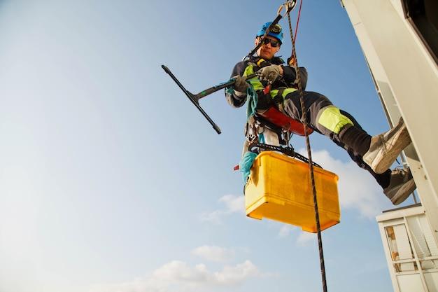 Pracownik alpinizmu przemysłowego wisi nad budynkiem mieszkalnym podczas mycia przeszklenia elewacji zewnętrznej. robotnik z dostępem linowym wisi na ścianie domu