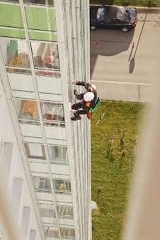 Pracownik alpinizmu przemysłowego wisi nad budynkiem mieszkalnym podczas mycia przeszklenia elewacji zewnętrznej