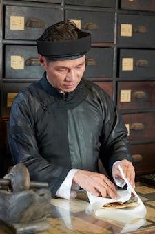 Pracownik apteki zawijający suche grzyby shiitake