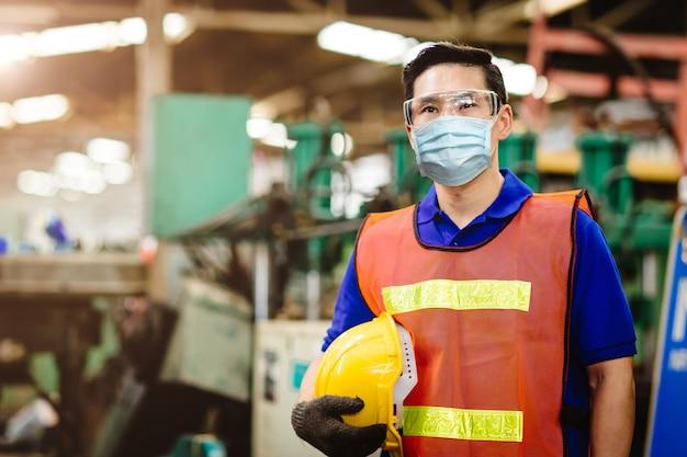 Pracownik azjatycki nosi w fabryce jednorazową maskę ochronną w celu ochrony przed rozprzestrzenianiem się wirusa wyładowań koronowych i filtrem zanieczyszczeń powietrza pyłem dymnym w fabryce w celu zapewnienia zdrowej pracy.