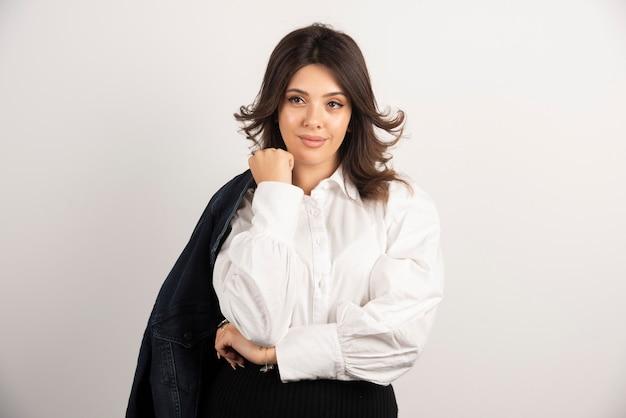 Pracownik biurowy kobieta trzymając kurtkę na ramionach.