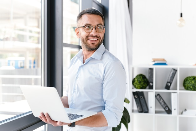 Pracownik biurowy mężczyzna ubrany w białą koszulę patrząc na bok, trzymając srebrny laptop podczas pracy w centrum biznesowym