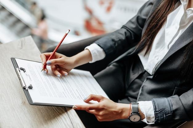 Pracownik biurowy młoda dziewczyna lub dama biznes podpisuje dokumenty. skoncentrowana bizneswoman pracuje z papierami. pomysł na biznes