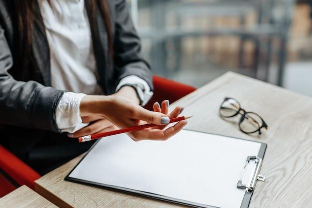 Pracownik biurowy młoda dziewczyna lub dama biznes podpisuje dokumenty