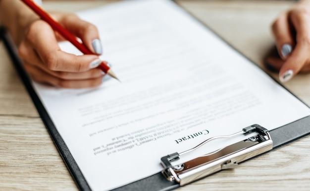 Pracownik biurowy młoda kobieta lub dama biznesowa podpisuje dokumenty
