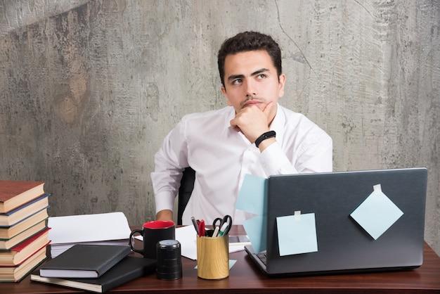 Pracownik biurowy myśli o pracy w biurze.