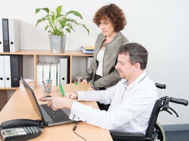 Pracownik biurowy niepełnosprawny mężczyzna na wózku inwalidzkim