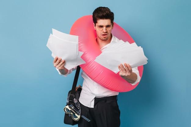 Pracownik biurowy patrzy na plik dokumentów z niezadowoleniem. facet jedzie na wakacje i pozuje z nadmuchiwanym kółkiem i maską do pływania.