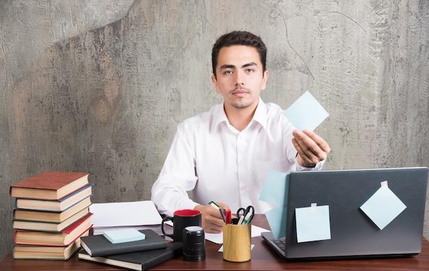 Pracownik biurowy pokazując notatnik w biurze informacji turystycznej.