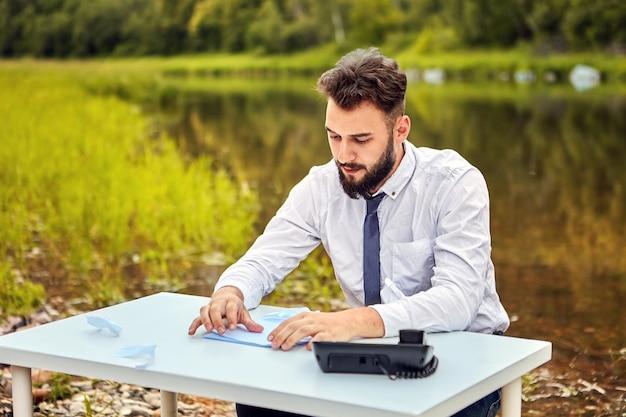 Pracownik biurowy siedzi przy stole z papierem i telefonem i fantazjuje, że jest na wolności.