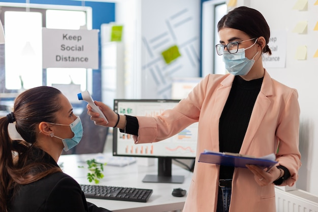Pracownik biurowy skanuje temperaturę kolegi, wskazując cyfrowy termometr na czole, zachowując dystans podczas globalnej pandemii z covid-19, nosząc maskę na twarz jako profilaktykę.