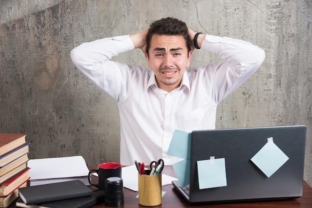 Pracownik biurowy, trzymając głowę, patrząc na kamery na biurku.