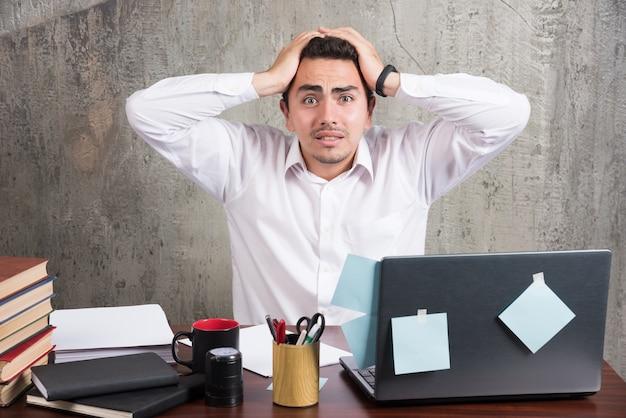 Pracownik biurowy trzymając głowę przy biurku.